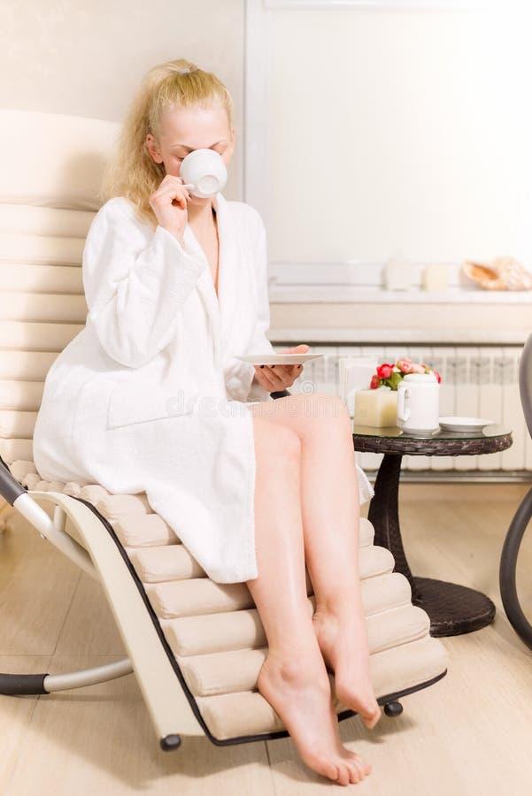 La chica joven bebe té en el salón del balneario mujer rubia en la capa blanca que sostiene una taza en sus manos fotografía de archivo libre de regalías