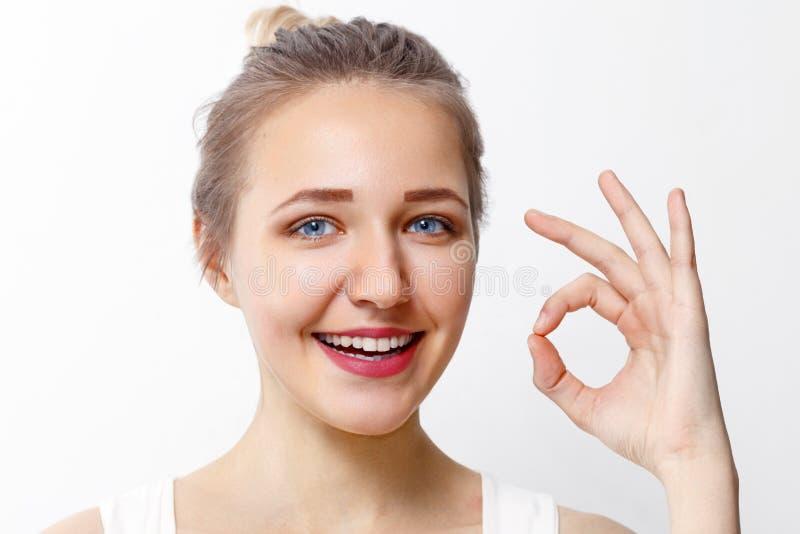 La chica joven bonita con maquillaje muestra gesto aceptable imagenes de archivo