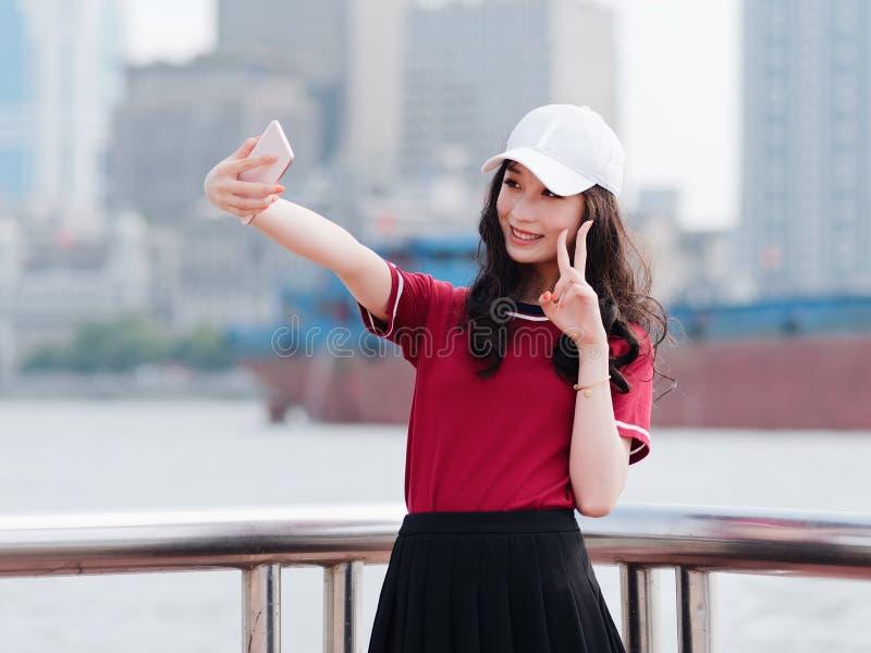 La chica joven bonita de la moda con el pelo largo negro, la camiseta roja que lleva y el selfie blanco de la gorra de béisbol co foto de archivo