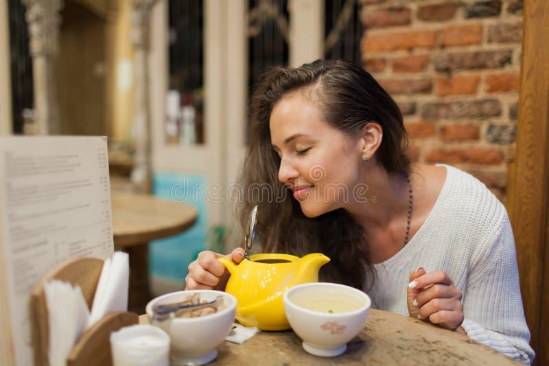 La chica joven bonita inhala el aroma del té recientemente preparado que se sienta en un café imágenes de archivo libres de regalías