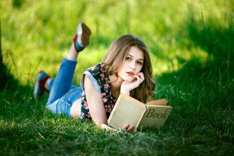 La chica joven caucásica atractiva leyó el libro que mentía en hierba verde fotos de archivo