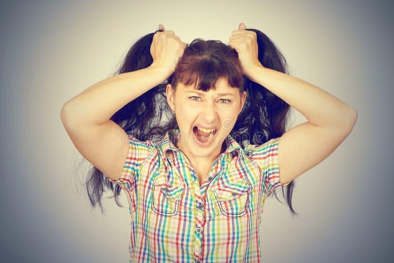 La chica joven caucásica loca enojada ase el pelo imágenes de archivo libres de regalías