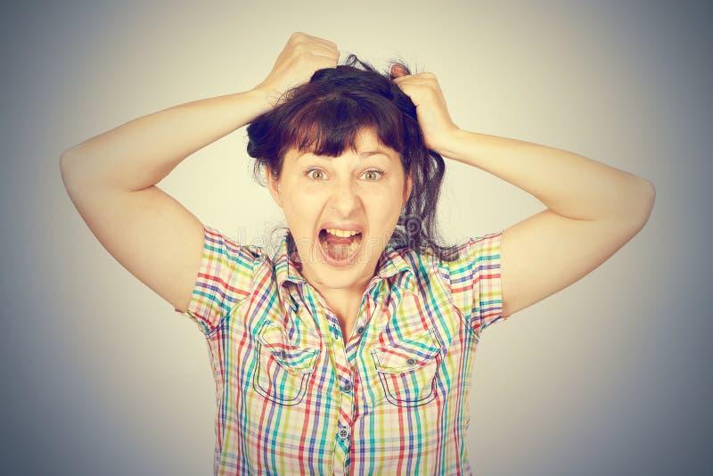 La chica joven caucásica loca enojada ase el pelo fotografía de archivo