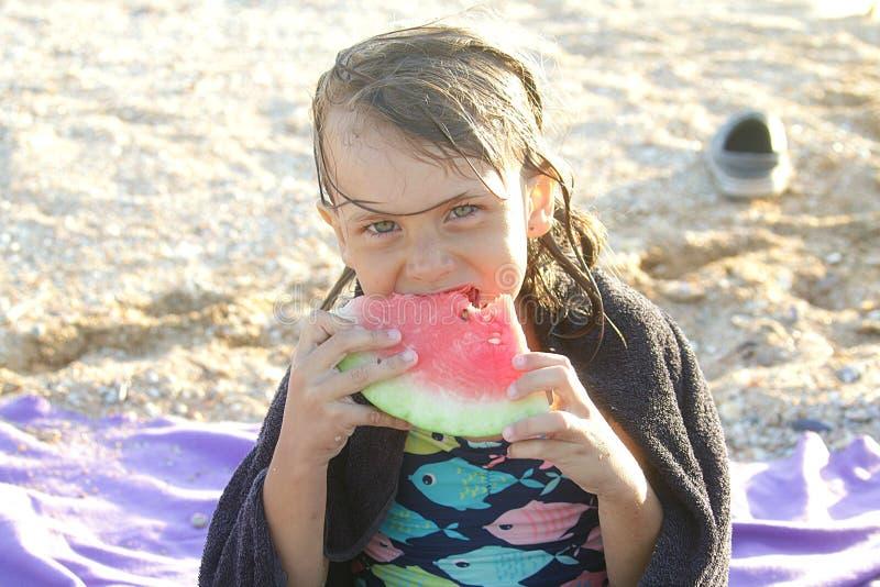 La chica joven come una rebanada de sandía en verano en la playa imagen de archivo libre de regalías