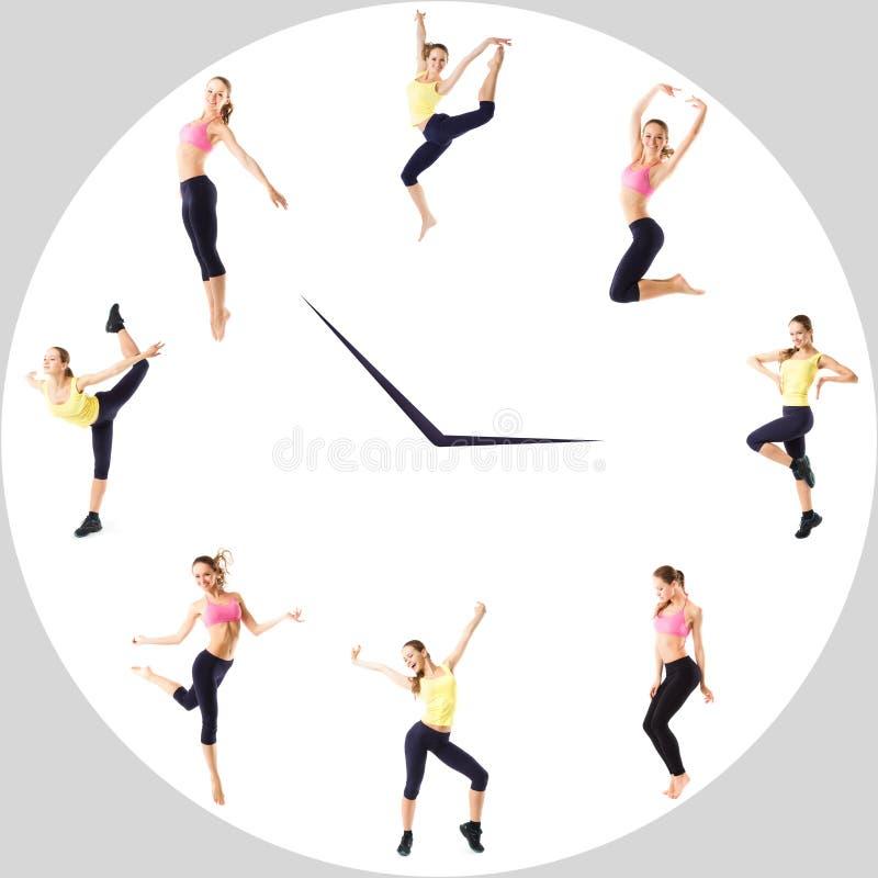 La chica joven con deportes perfectos figura en el reloj del círculo Concepto del deporte - tiempo de la aptitud imagenes de archivo