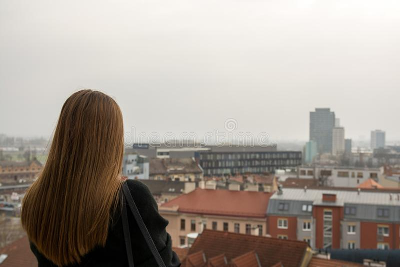 La chica joven con el abrigo de invierno está mirando en la ciudad imágenes de archivo libres de regalías