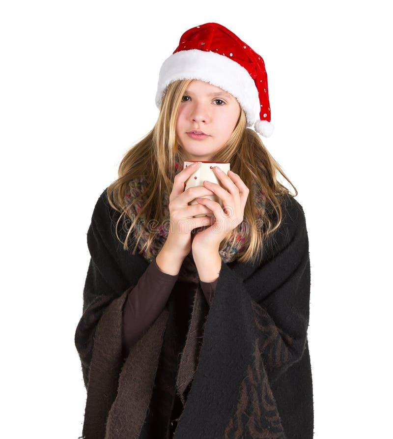 La chica joven con el cabo negro y el invierno rojo capsulan sostener la taza imagen de archivo