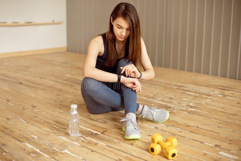 La chica joven con el pelo oscuro se sienta en el piso y puso a su perseguidor de la aptitud al entrenamiento en el gimnasio imagen de archivo