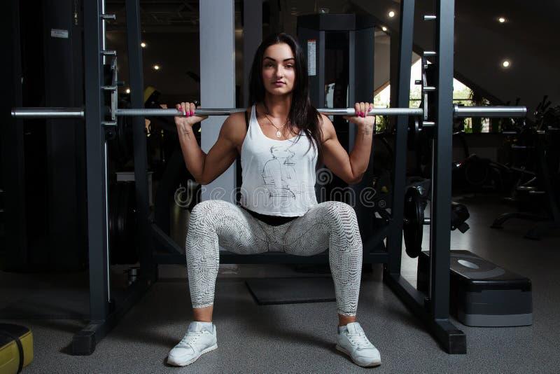La chica joven con la figura inflada sexual, en el gimnasio, se pone en cuclillas con imagenes de archivo