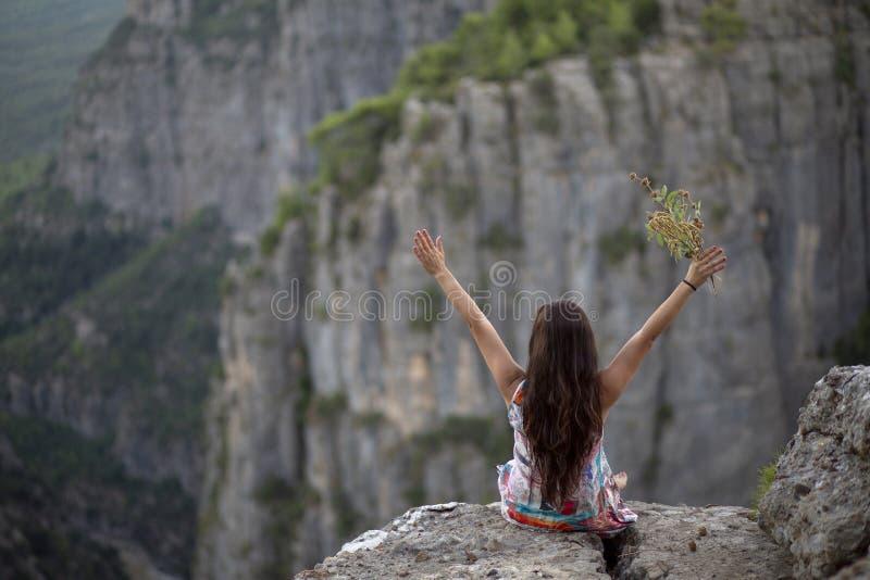 La chica joven con las flores en su mano, que hizo una muestra de la victoria mientras que miraba la opinión del barranco imagen de archivo