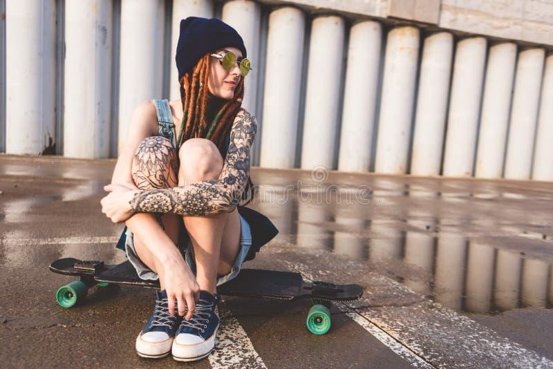 La chica joven con los tatuajes y los dreadlocks en un casquillo azul se sienta en un longboard contra la perspectiva de la estru fotos de archivo