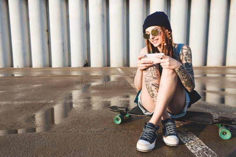 La chica joven con los tatuajes y los dreadlocks en un casquillo azul utiliza un smartphone contra la perspectiva de un muro de c foto de archivo libre de regalías