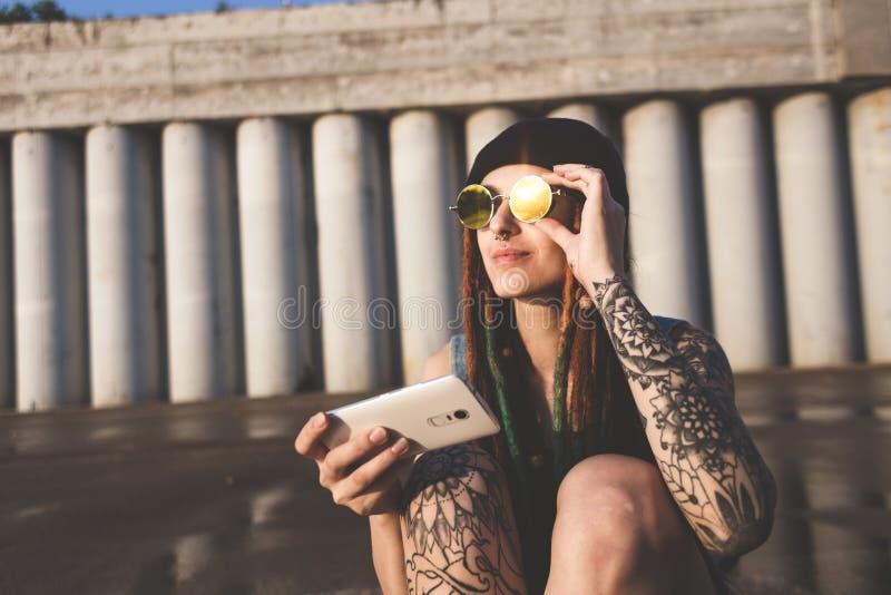 La chica joven con los tatuajes y los dreadlocks en un casquillo azul utiliza un smartphone contra la perspectiva de un muro de c foto de archivo