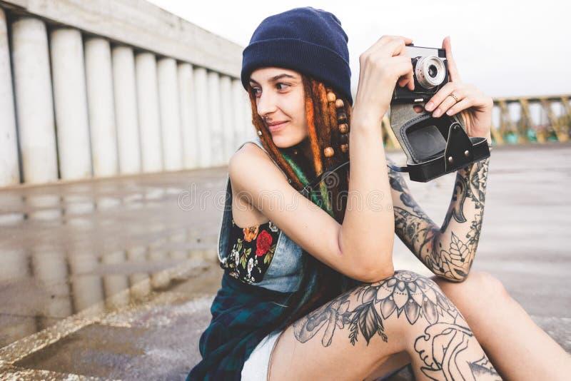 La chica joven con los tatuajes y los dreadlocks en un sombrero del azul fotografía una cámara del vintage en el fondo de un muro imagenes de archivo