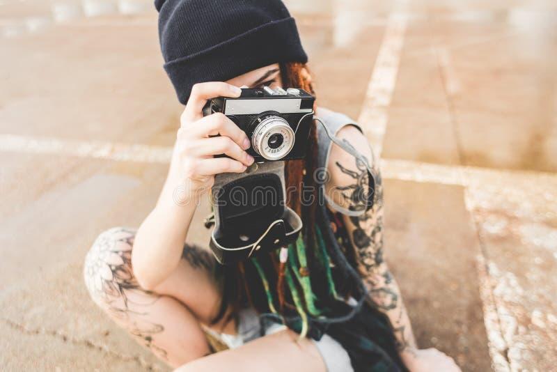 La chica joven con los tatuajes y los dreadlocks en un sombrero del azul fotografía una cámara del vintage en el fondo de un muro imágenes de archivo libres de regalías