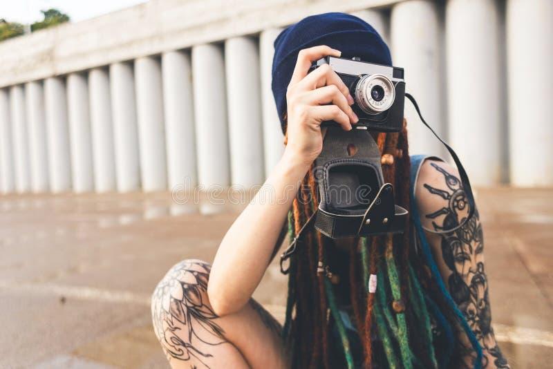 La chica joven con los tatuajes y los dreadlocks en un sombrero del azul fotografía una cámara del vintage en el fondo de un muro fotografía de archivo