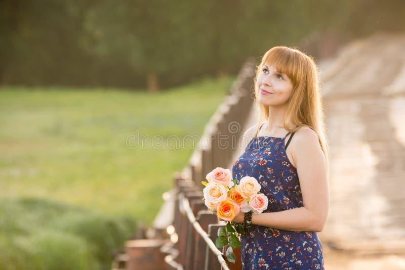 La chica joven con un ramo de rosas que se colocaban en el puente en el fondo empañó follaje imagen de archivo libre de regalías