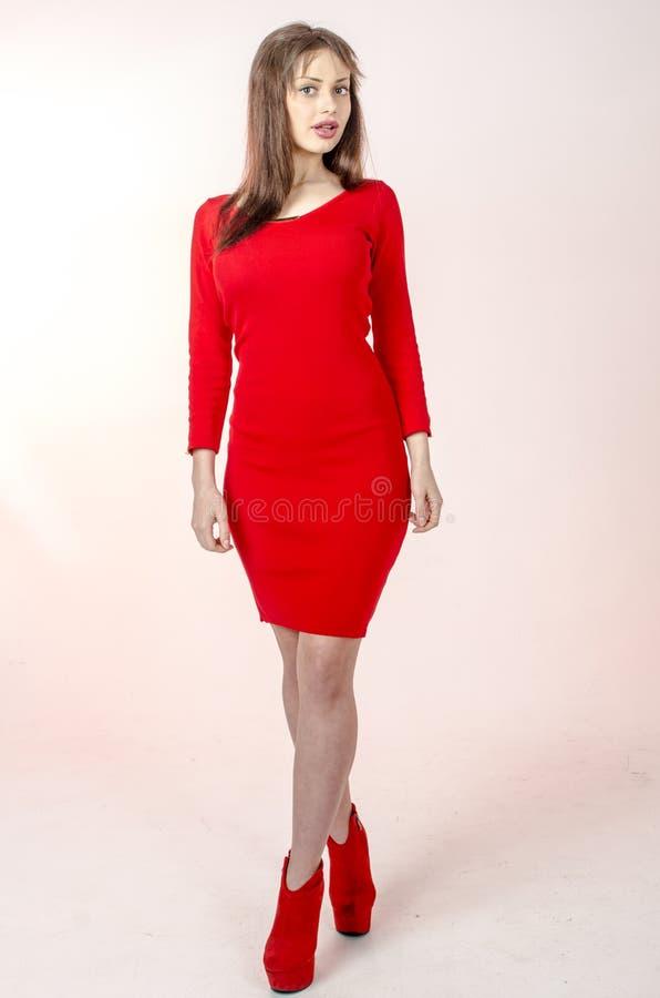 La chica joven con una figura hermosa en un vestido rojo de moda en miniskirt ceñido y los tacones altos y plataforma rojos se vi fotos de archivo libres de regalías