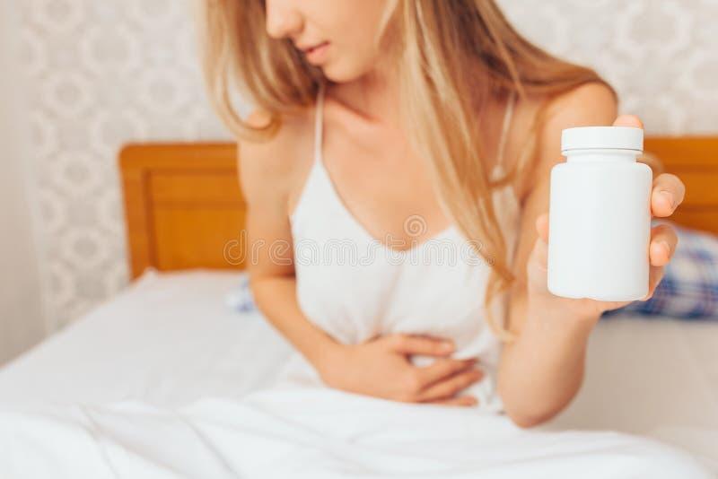 La chica joven da sostenerse el vientre, y sostiene píldoras en su mano imágenes de archivo libres de regalías