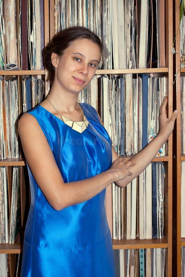 La chica joven de 20 años en vestido azul es estante cercano derecho con imagenes de archivo