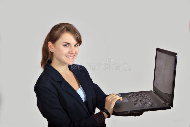 La chica joven del pelirrojo está trabajando en un ordenador portátil aislado en fondo gris imagen de archivo