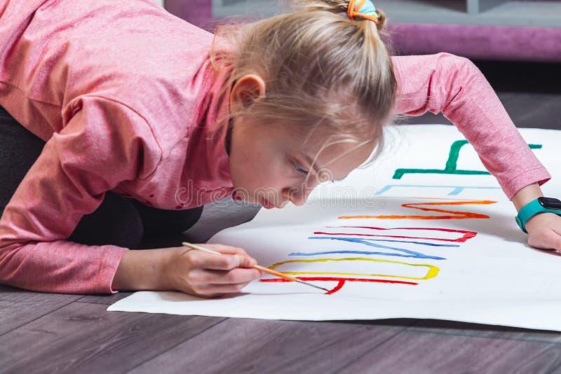 La chica joven dibuja en el piso con las pinturas en el papel fotografía de archivo libre de regalías