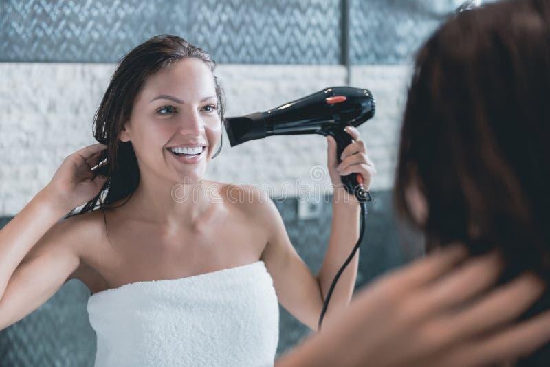 La chica joven el secador del cabello seco después de regar fotos de archivo