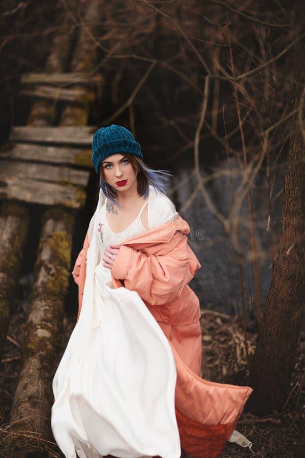 La chica joven elegante camina a lo largo del río, cerca de un pequeño puente de madera foto de archivo