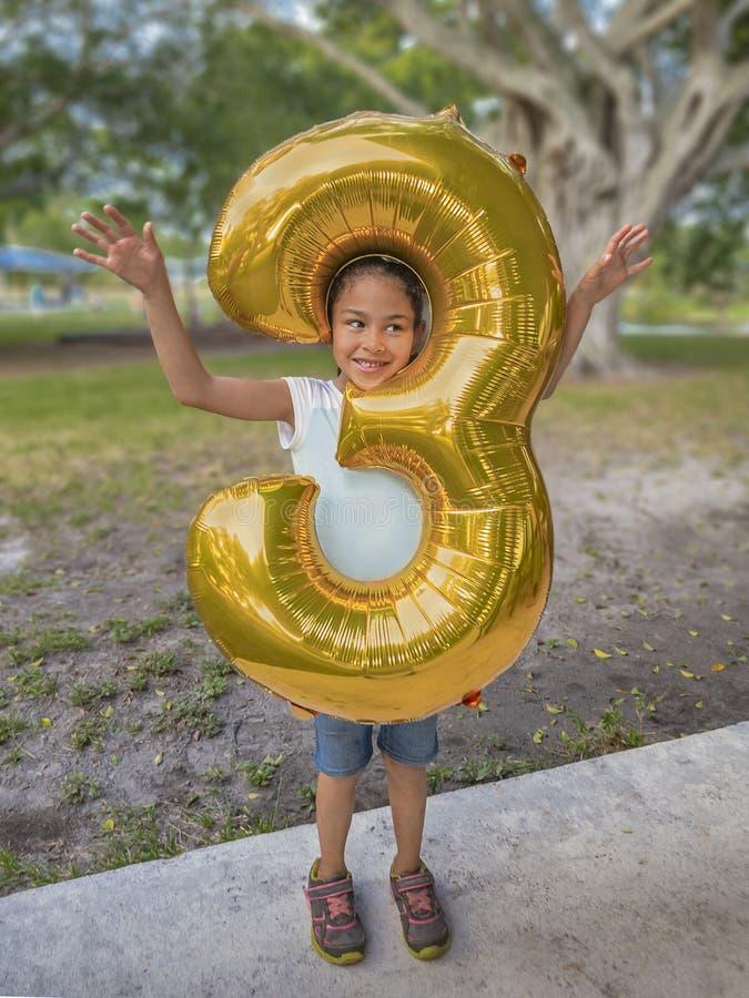 La chica joven empuja su cabeza a través de un globo metálico del oro del gran número tres fotos de archivo libres de regalías