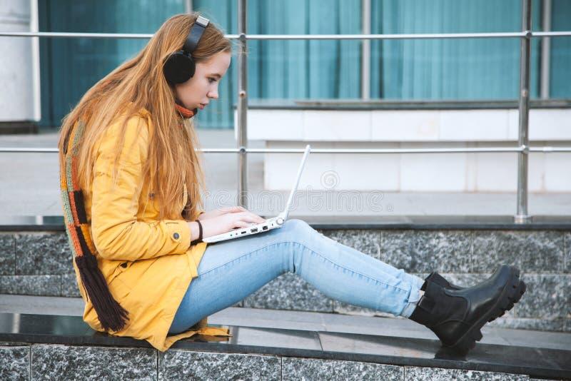 La chica joven en auriculares sostiene un ordenador portátil, sentándose en los pasos de la universidad imagenes de archivo