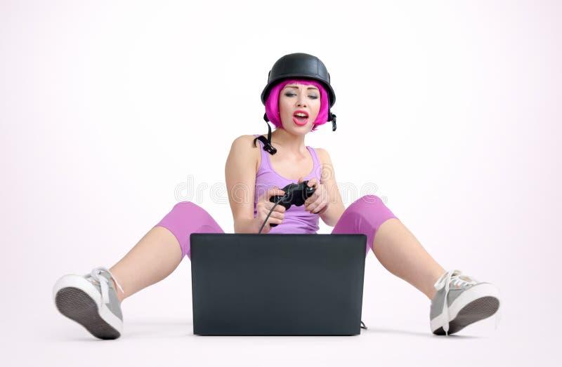 La chica joven en el casco con la palanca de mando se sienta en el piso y juego el jugar en un ordenador portátil imagen de archivo
