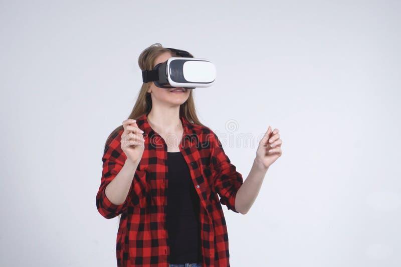 La chica joven en el casco de la realidad virtual está jugando activamente al juego fotografía de archivo