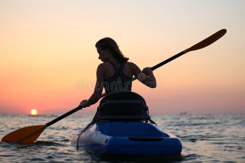 La chica joven en el kajak saluda el amanecer del sol fotografía de archivo