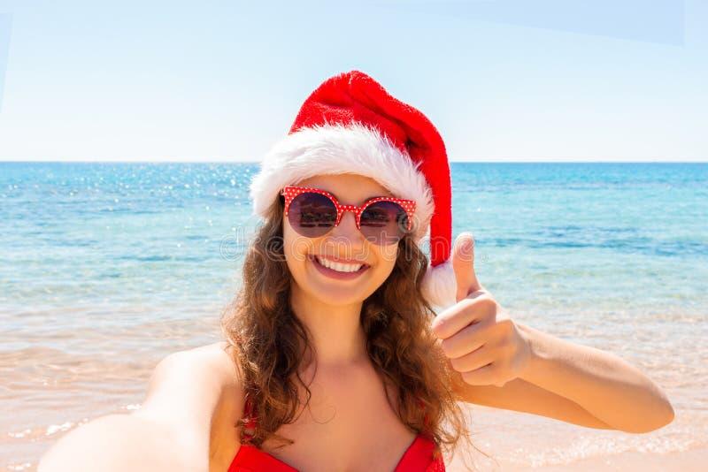 La chica joven en el sombrero de santa muestra el upand del pulgar que se divierte que toma imágenes del selfie del smartphone de fotografía de archivo