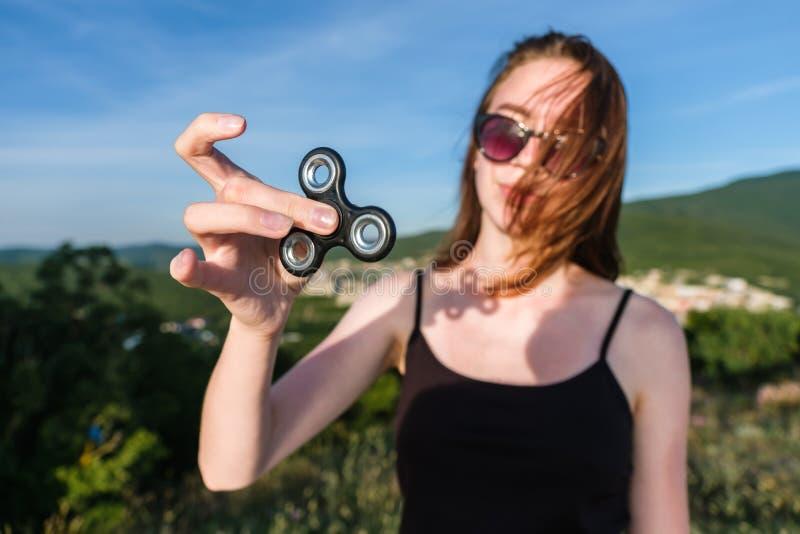 La chica joven en gafas de sol coloca en los controles de una montaña a un hilandero en su mano y lo mira vista delantera foto de archivo libre de regalías