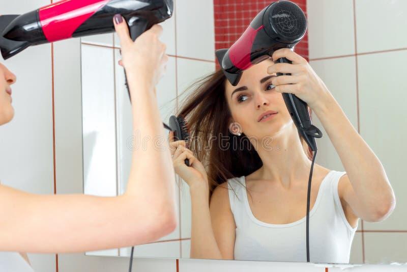 La chica joven en la camisa blanca se coloca cerca del espejo y el cabello seco imagen de archivo libre de regalías