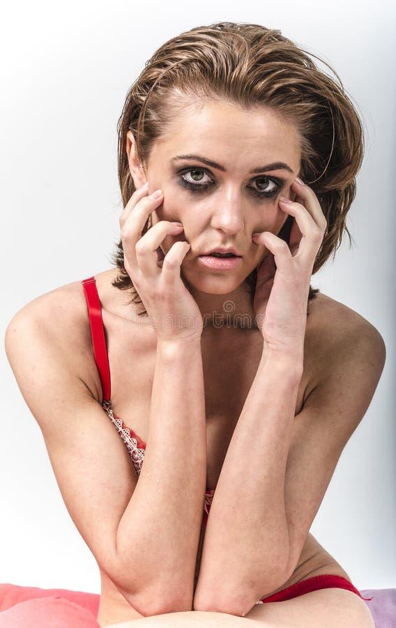 La chica joven en ropa interior en cama que llora y que limpia rasga manchar sus manos imagen de archivo libre de regalías
