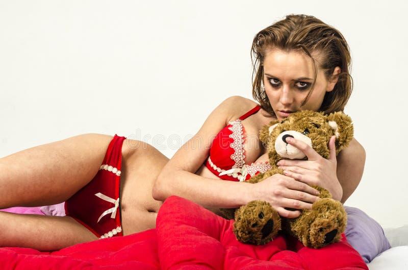 La chica joven en ropa interior en cama que llora y que limpia rasga manchar sus manos foto de archivo libre de regalías