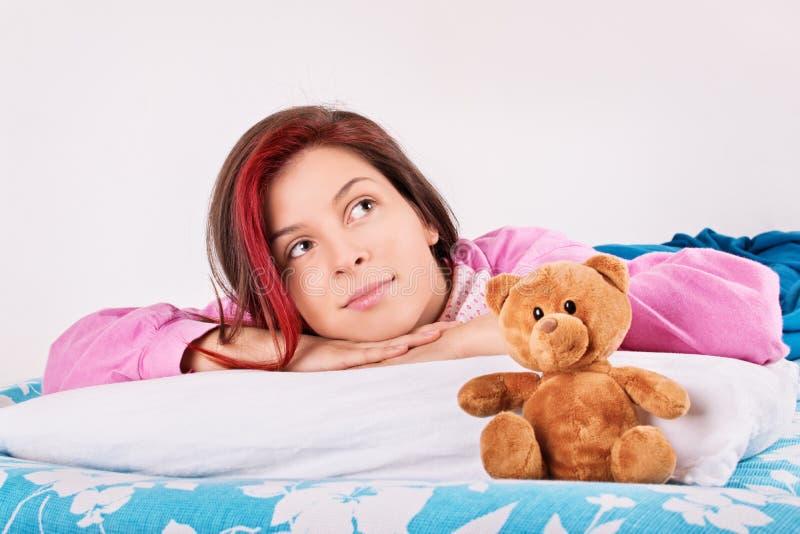 La chica joven en su cama, se despierta con su oso de peluche imagen de archivo