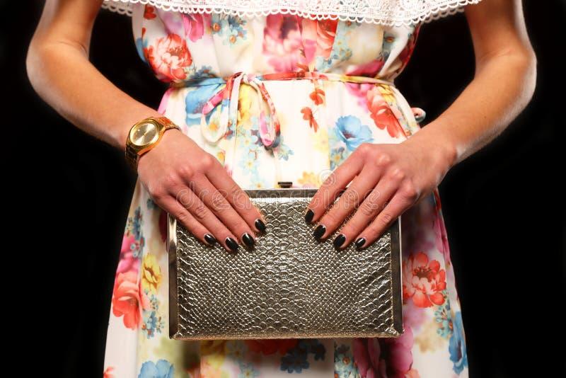 La chica joven en un vestido colorido está sosteniendo su bolso elegante imágenes de archivo libres de regalías