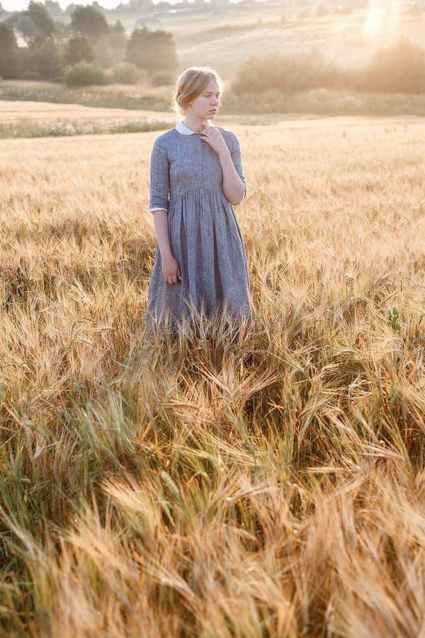 La chica joven en vestido azul con actitudes recogidas del pelo, considera lejos en el campo de oídos la salida del sol Amanecer  foto de archivo