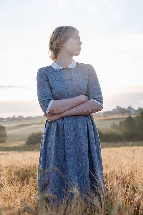 La chica joven en vestido azul con actitudes recogidas del pelo, considera lejos en el campo de oídos la salida del sol Amanecer  imagenes de archivo