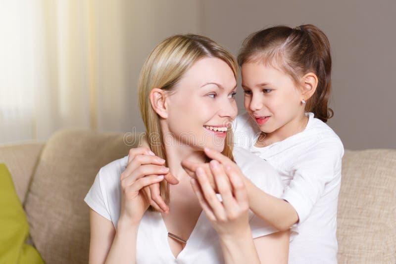 La chica joven es cerrada sus ojos de la madre La madre hermosa y su pequeña hija están sonriendo imagen de archivo libre de regalías