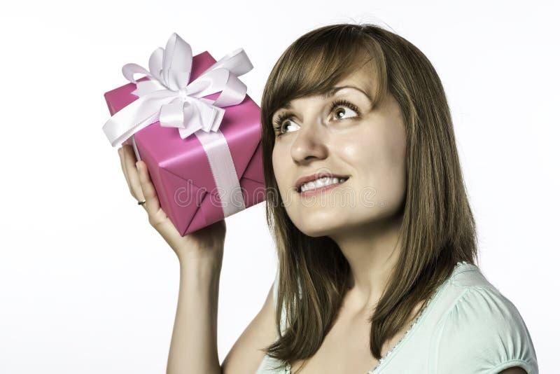 La chica joven escucha un regalo imagen de archivo libre de regalías