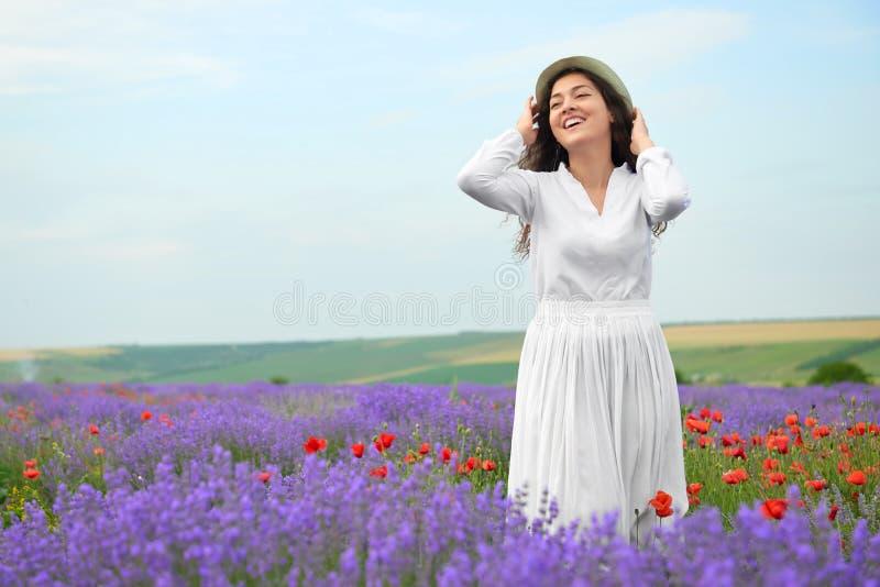 La chica joven está en el campo de la lavanda, paisaje hermoso del verano con las flores foto de archivo