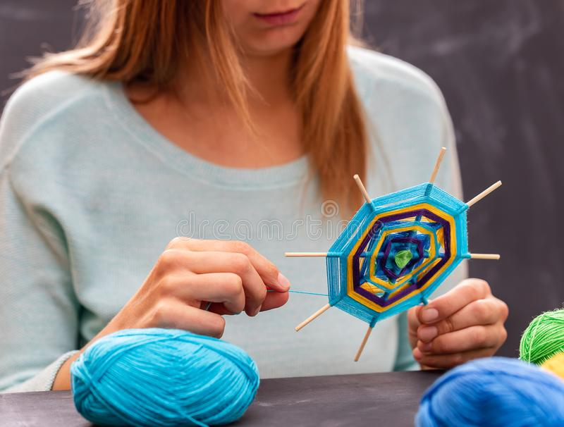 La chica joven está haciendo la mandala hecha a mano fuera del hilado coloreado imagen de archivo libre de regalías