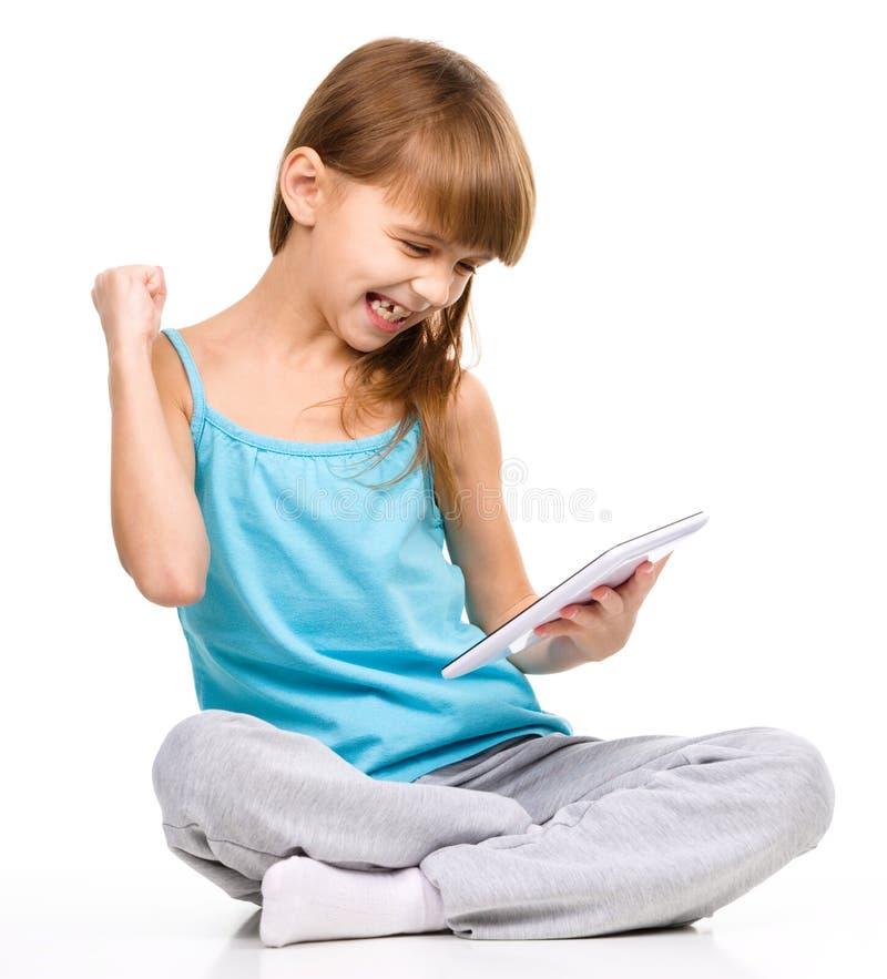 La chica joven está jugando al juego usando la tableta imagenes de archivo