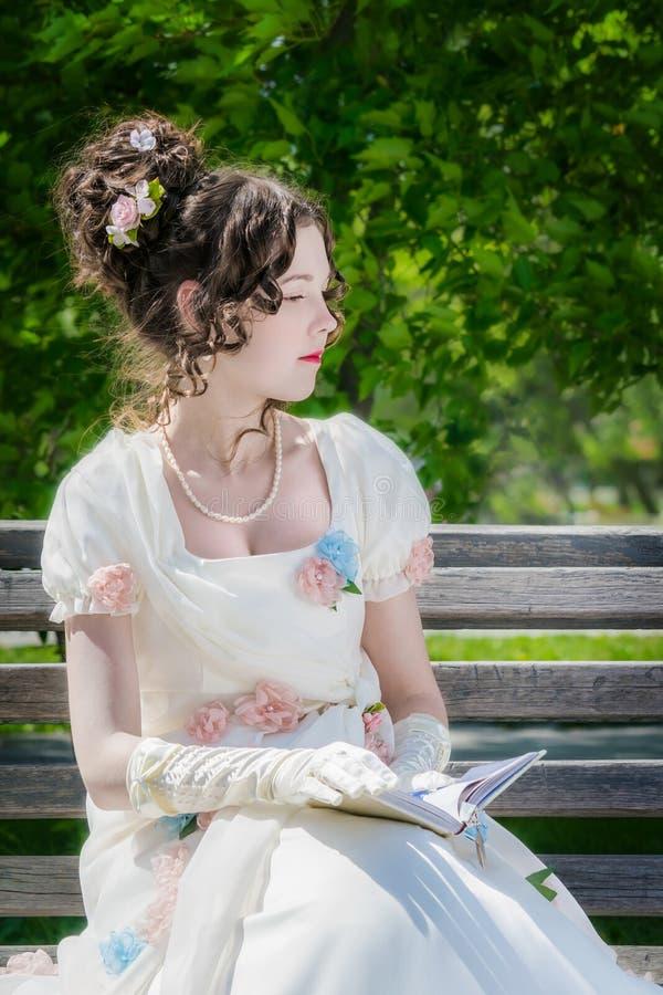 La chica joven está leyendo un libro que se sienta en un banco fotos de archivo libres de regalías