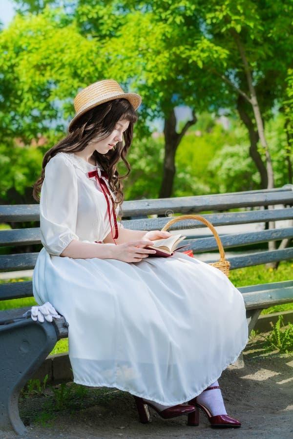 La chica joven está leyendo un libro que se sienta en un banco imágenes de archivo libres de regalías