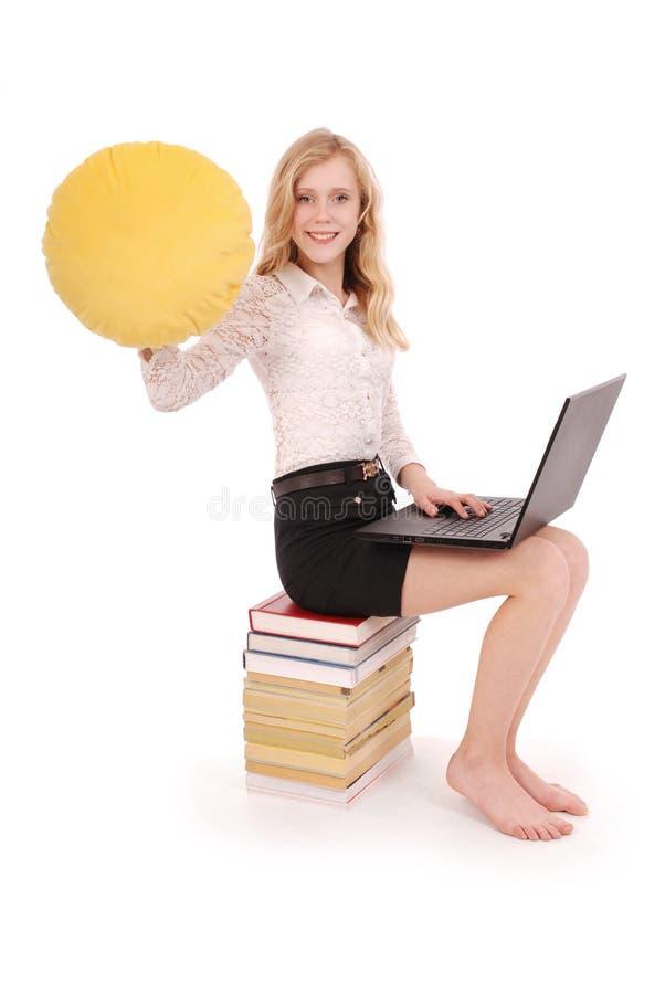 La chica joven está sosteniendo una almohada sonriente de la cara fotos de archivo libres de regalías